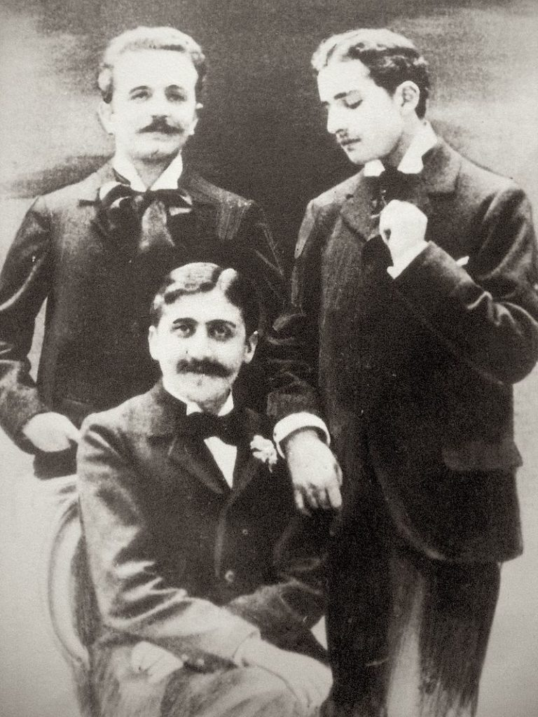 Marcel Proust (seated), Robert de Flers (left), and Lucien Daudet (right)