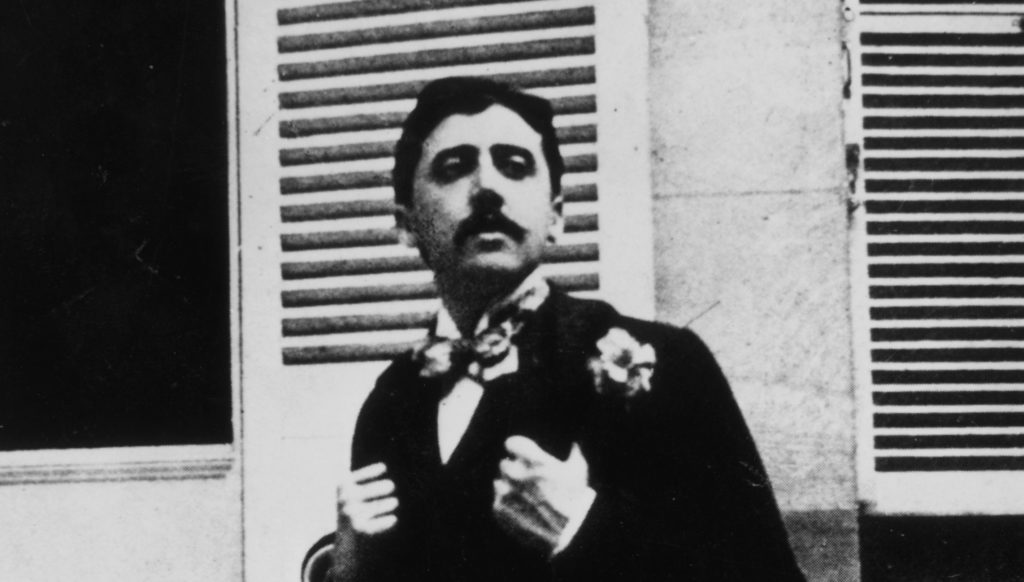 French author Marcel Proust sitting outside a window.