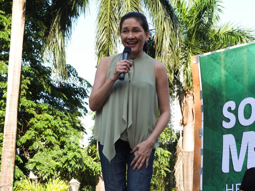 Risa Hontiveros smiling as she speaks into a microphone