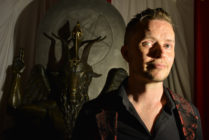 Lucien Greaves, spokesman for The Satanic Temple, with a statue of Baphomet at the group's meeting house in Salem, Massachusetts.