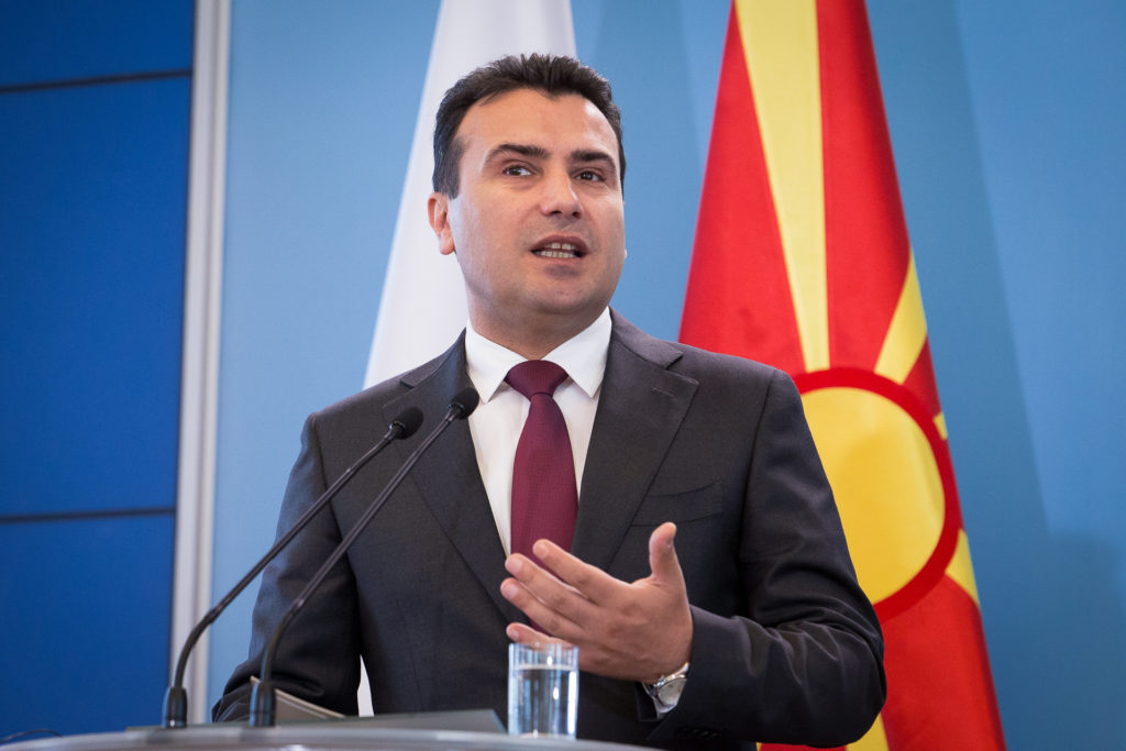 Zoran Zaev speaking in front of a North Macedonia flag.