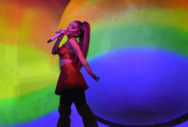 Ariana GRnade singing in front of a rainbow
