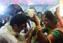 A bride places a garland over her groom's head