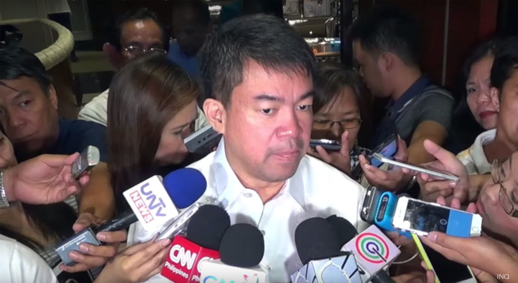 Koko Pimintel surrounded by microphones