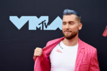 Lance Bass pulling his jacket aside to show the 'Tearin' Up My Heart' message on his t-shirt