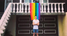Daniel Comesoli outside of his apartment with a rainbow hanging from his balcony.