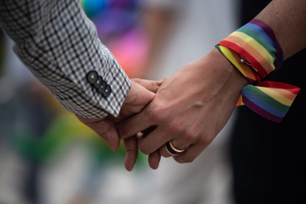 A close-up of a same-sex couple holding hands, one has a rainbow ribbon wrapped around their wrist