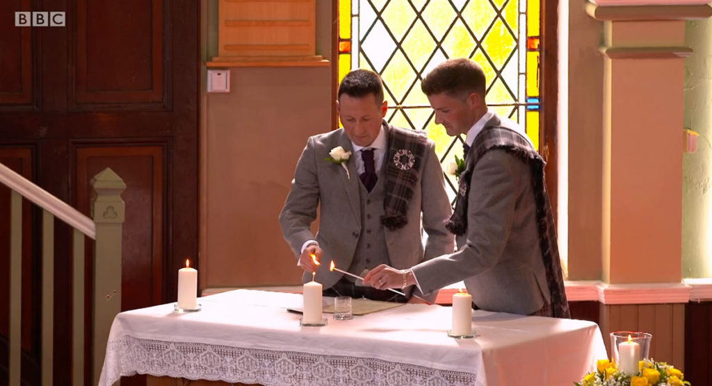 Jamie Wallace and Ian McDowall lighting a candle together.