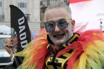 "Pride participant seen with rainbow feathers and a ""Daddy"" fan"
