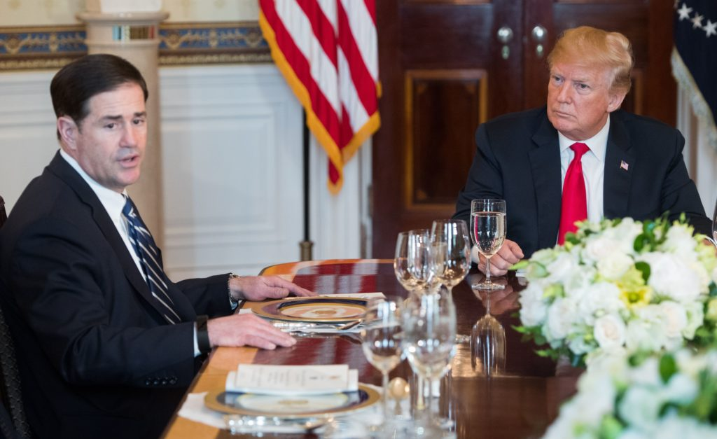 Arizona governor Doug Ducey speaks beside US President Donald Trump during a dinner with US state governors