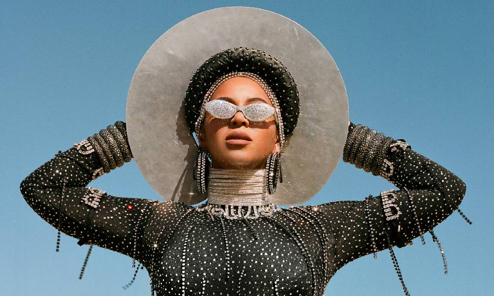Beyoncé in Black is King wearing bejewelled sunglasses, a white wide-brimmed hat and a sparkly black body stocking