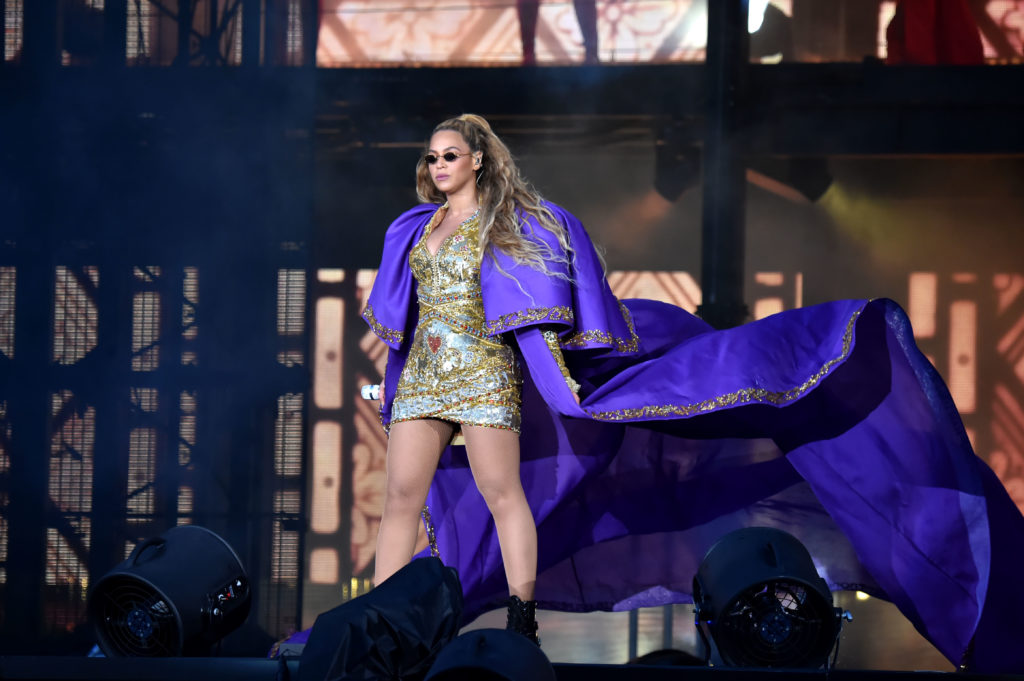Beyoncé in a gold dress and a long purple cape