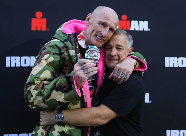 Gareth Thomas shows his finishers medal as he celebrates with his partner on completing his first Ironman triathlon. (Huw Fairclough/Getty Images)