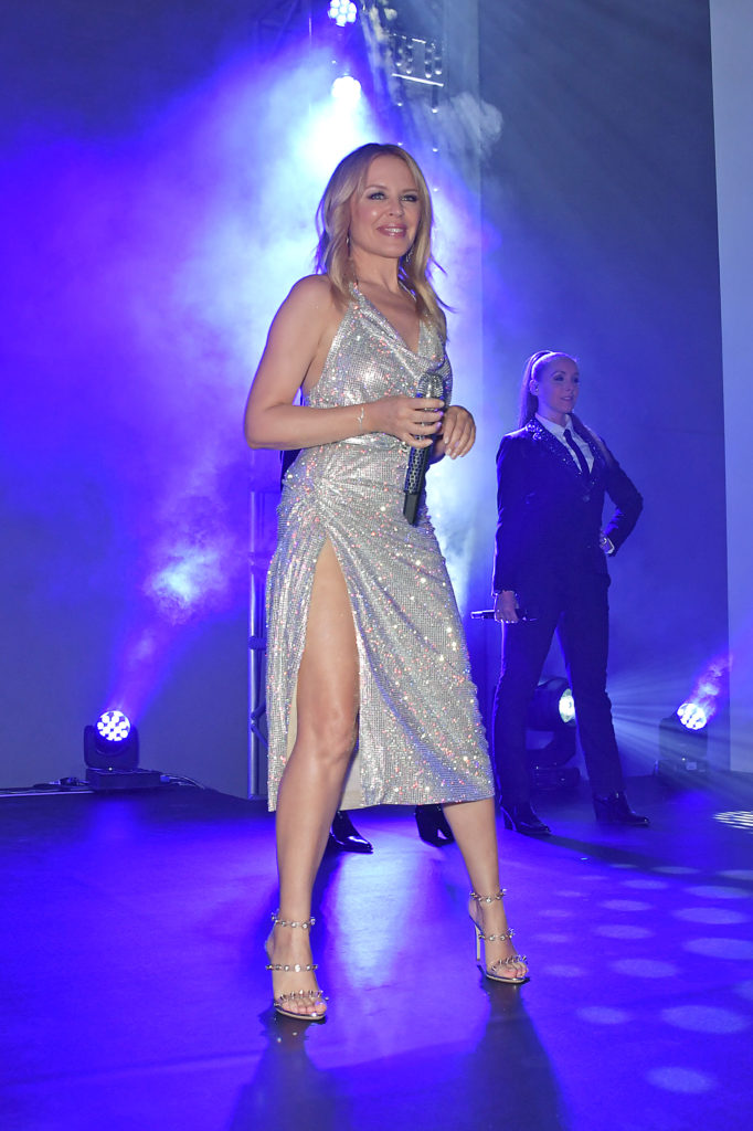 Kylie Minogue on stage in a silver glittery dress
