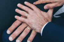 Two male hands touching, both wearing wedding rings