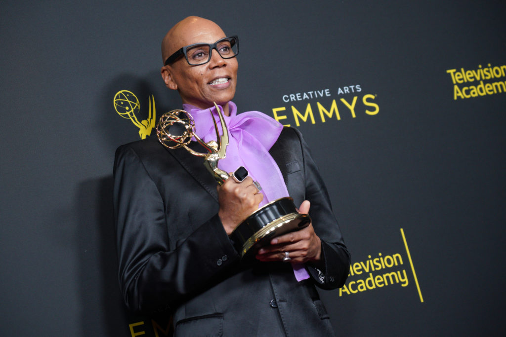 RuPaul holding his Emmy Award, wearing a black jacket and a purple pussy bow