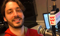 Gay radio host Seth Dunlap speaking into a radio microphone