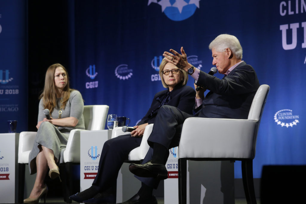 Chelsea Clinton (L), and former Secretary of State Hillary Clinton (C) listens as former President Bill Clinton speaks. (Joshua Lott/Getty Images)