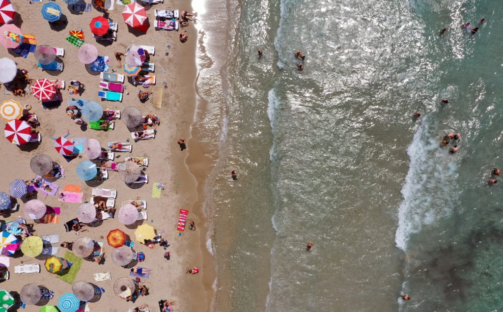 A drone photo shows the aerial view of a beach as people sunbathe under colourful parasols and swim in the sea in Kusadasi district of Aydin, Turkey. (Ferdi Uzun/Anadolu Agency via Getty Images)