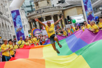 A general view a flag bearer jumping on the giant Pride flag during Pride in London 2019 on July 06, 2019 in London, England.