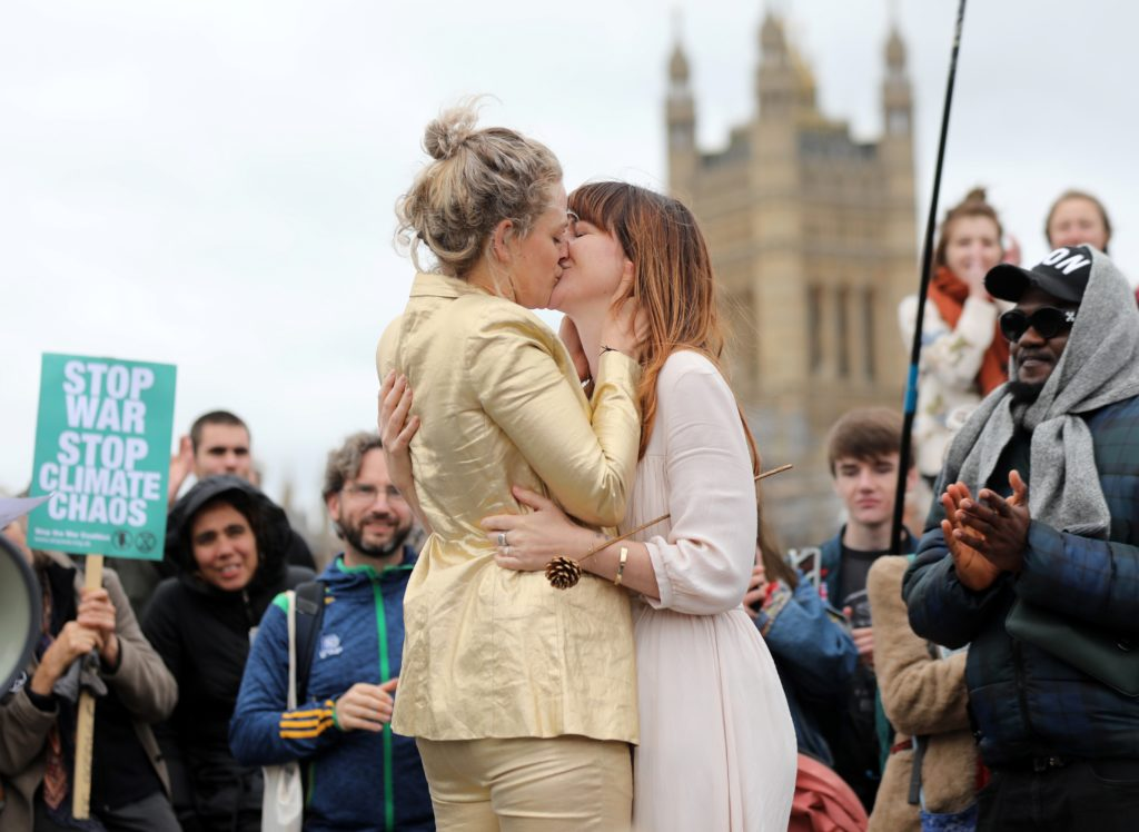 Tasmin and Melissa embrace after they received a blessing ahead of their wedding day, surrounded by activists from the climate change group Extinction Rebellion, during a demonstration on Westminster Bridge