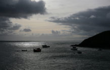 View out to sea from Creux Harbour on Sark, showing fishing boats in silhouette on a grey sea with a cloudy grey sky, 21st November 2008
