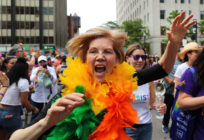 Elizabeth Warren in rainbow feather boa