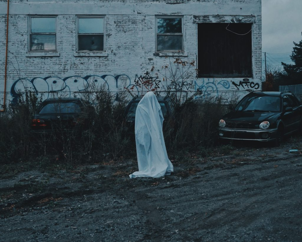 A ghost lurks in a run-down parking lot, looking for a queer person to inhabit. Truly haunting. (Stock photo via UnSplash)
