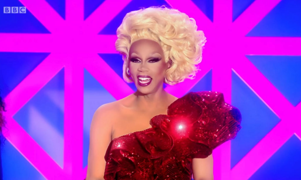 RuPaul in a one-shouldered sequinned red dress and a blonde updo, smiling behind the Drag Race UK judging table