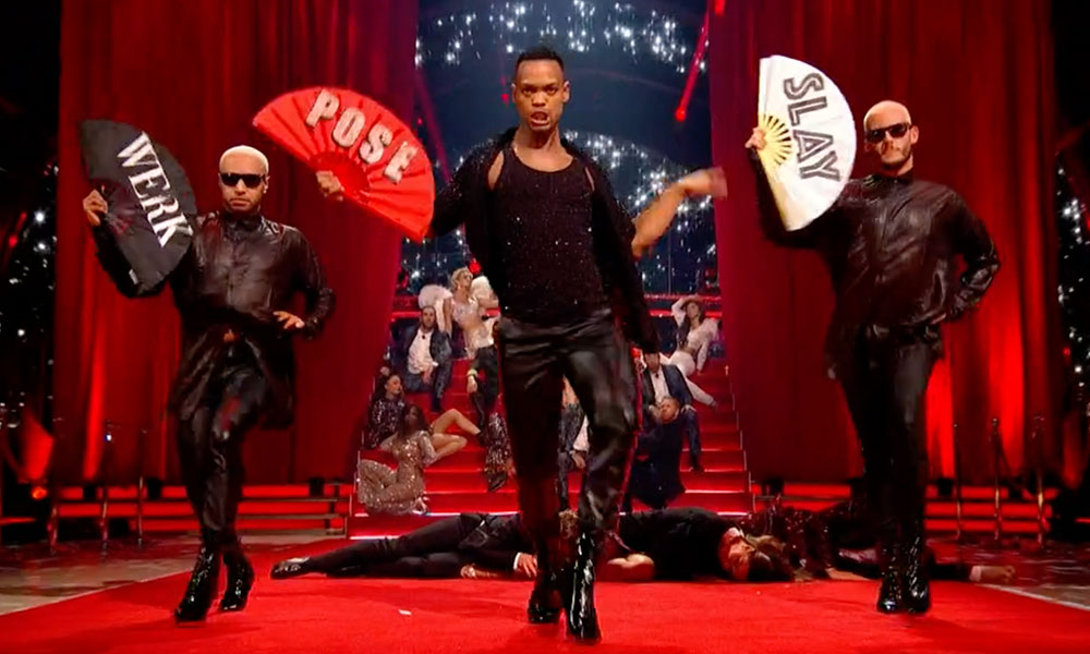 Johannes Radebe and two dancers in heels holding hand fans