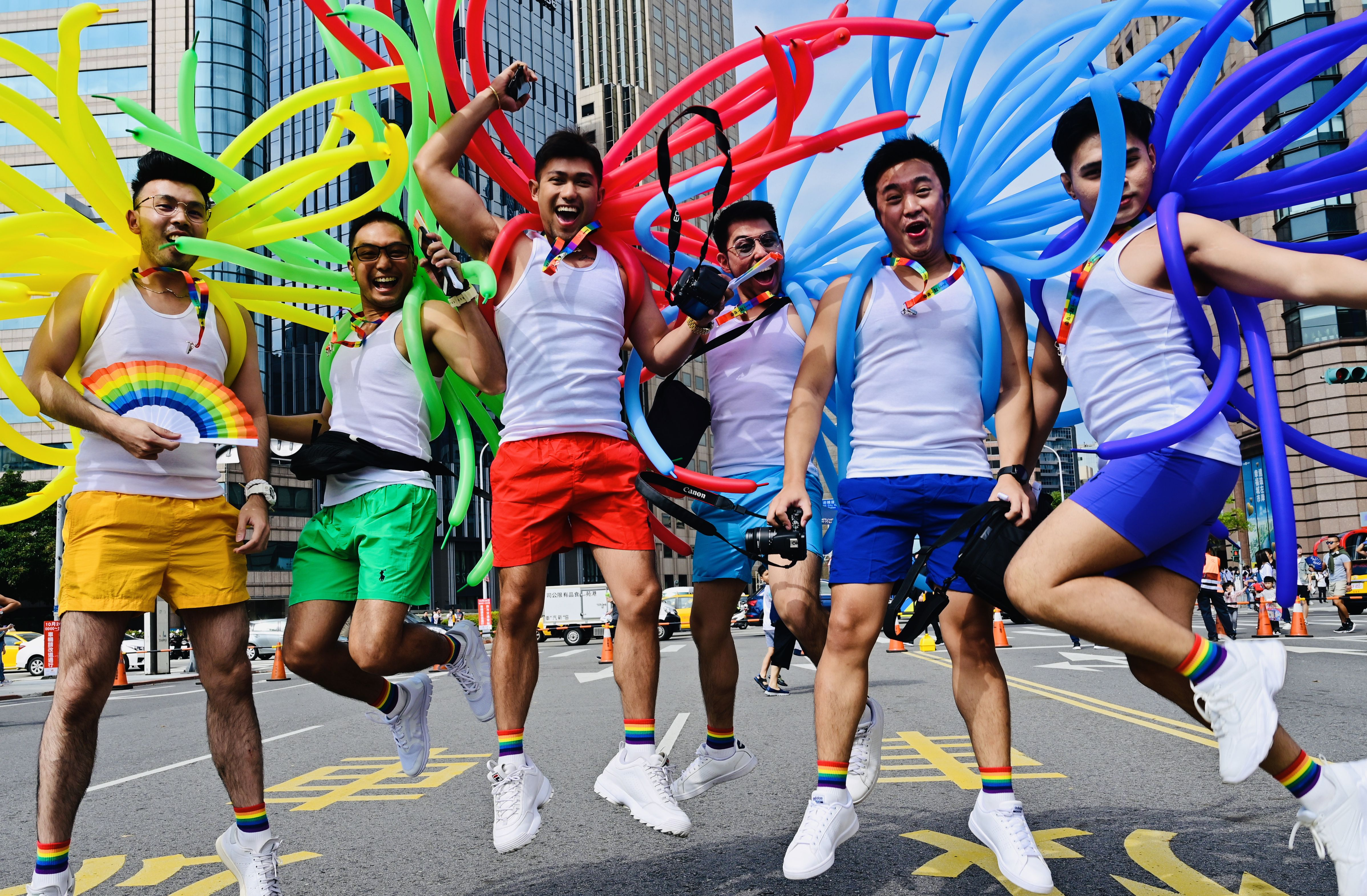 A group of men in white vests and shorts. Each holds balloons in a different colour of the rainbow.