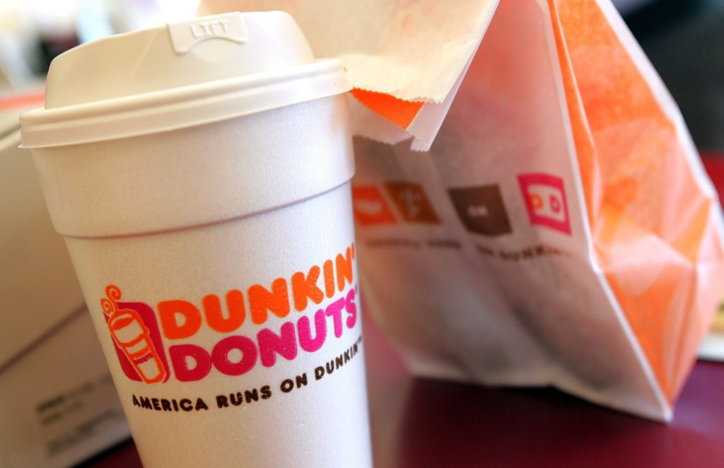 A cup of Dunkin' Donuts coffee and a donut bag sit on a counter. (Tim Boyle/Getty Images)