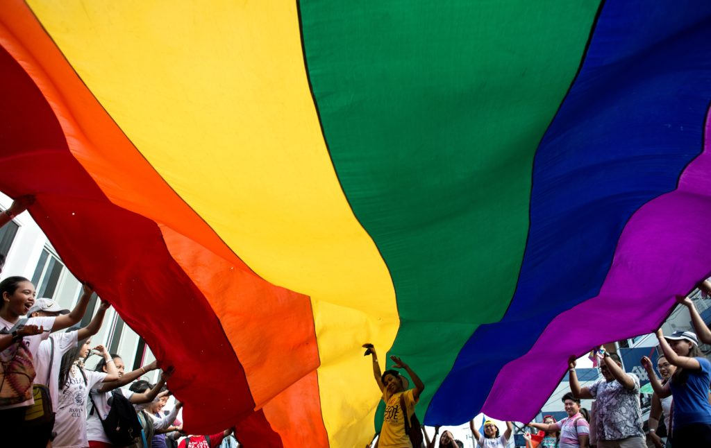Participants parade a LGBT+ flag during a Pride pride march in Manila. (NOEL CELIS/AFP via Getty Images)