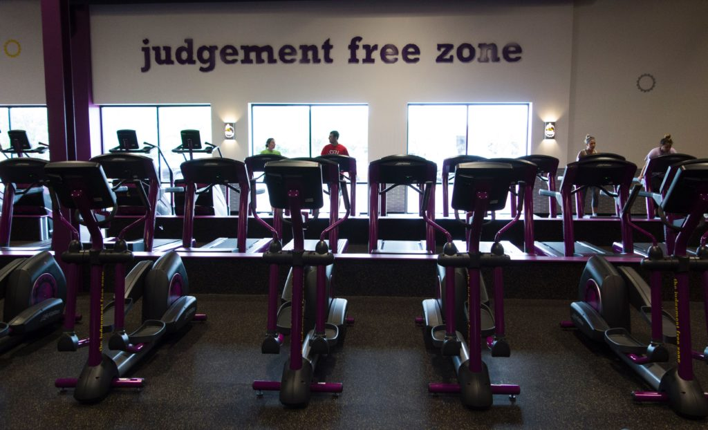 People exercise at Planet Fitness with the sign 'Judgement Free Zone' on the wall. IDON EMMERT/AFP via Getty Images)