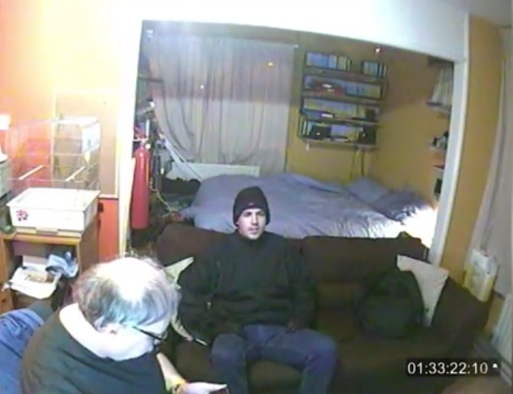 Jason Marshall, dressed as an MI5 agent, chats to Peter Fasoli in his West London apartment. (Screen capture via Metropolitan Police)