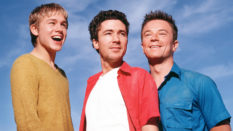 Nathan, Stuart and Vince from Queer as Folk, smiling against a blue sky