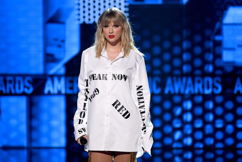 Taylor Swift wearing a shirt with the names of her first six albums at the AMAs