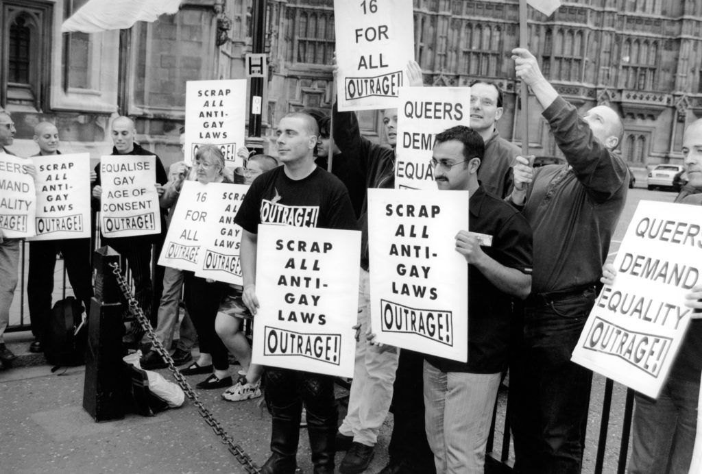 protesters holding placards with messages reading 'equalise gay age of consent' and scrap all anti-gay laws'