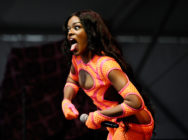 Azealia Banks poses while performing at the 2013 Governors Ball Music Festival in an orange dress