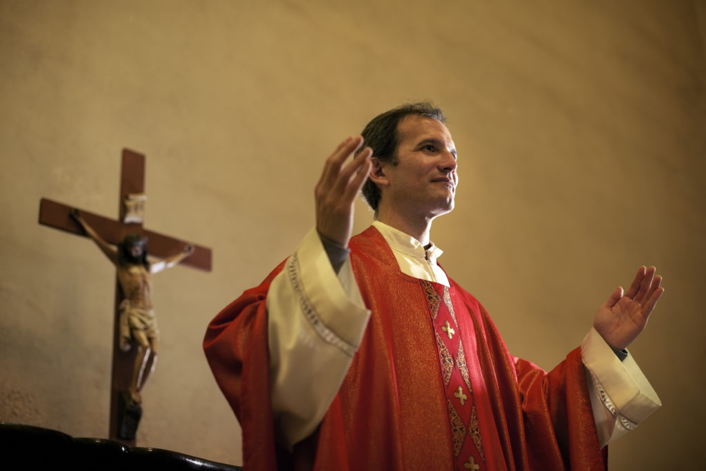 Catholic priest on altar praying with open arms during mass service in church. (Stock photo via Elements Envato)