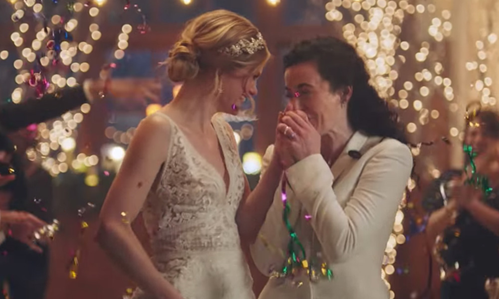 Two brides walking down the aisle, one is kissing the other's hand