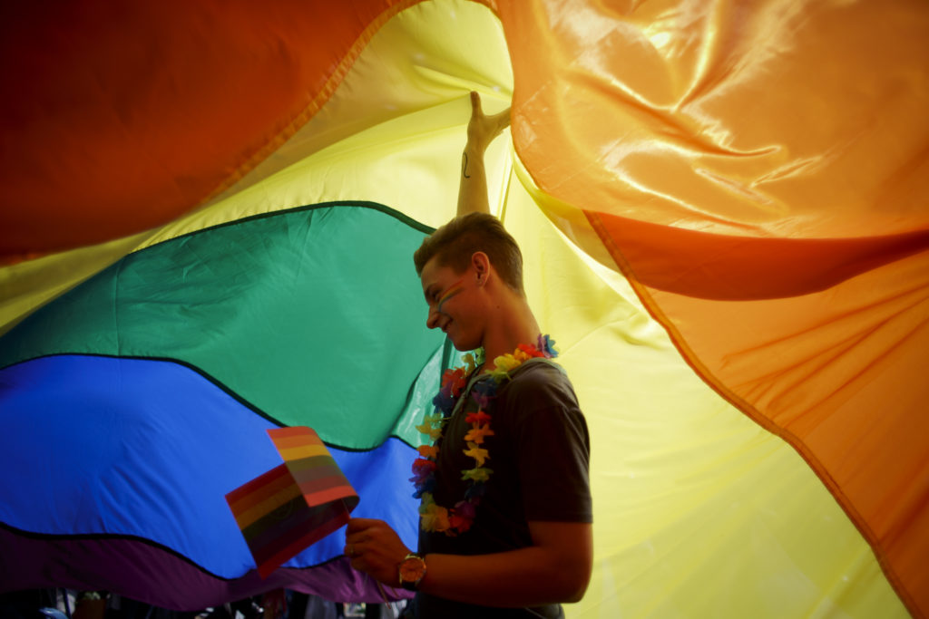 Participant dances as he holds up a large rainbow flag during the third Prague Pride March on August 17, 2013 in Prague, Czech Republic. (Matej Divizna/Getty Images)