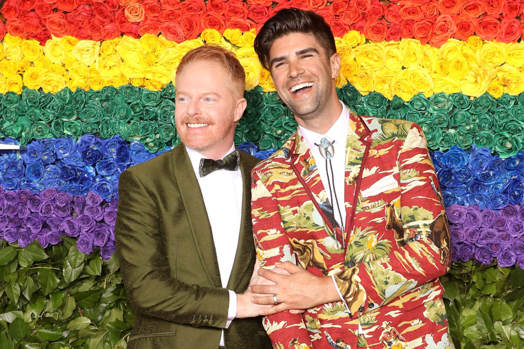 Jesse Tyler Ferguson and his husband Justin Mikita in front of a rainbow flower wall
