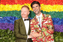 Modern Family Jesse Tyler Ferguson and his husband Justin Mikita in front of a rainbow flower wall