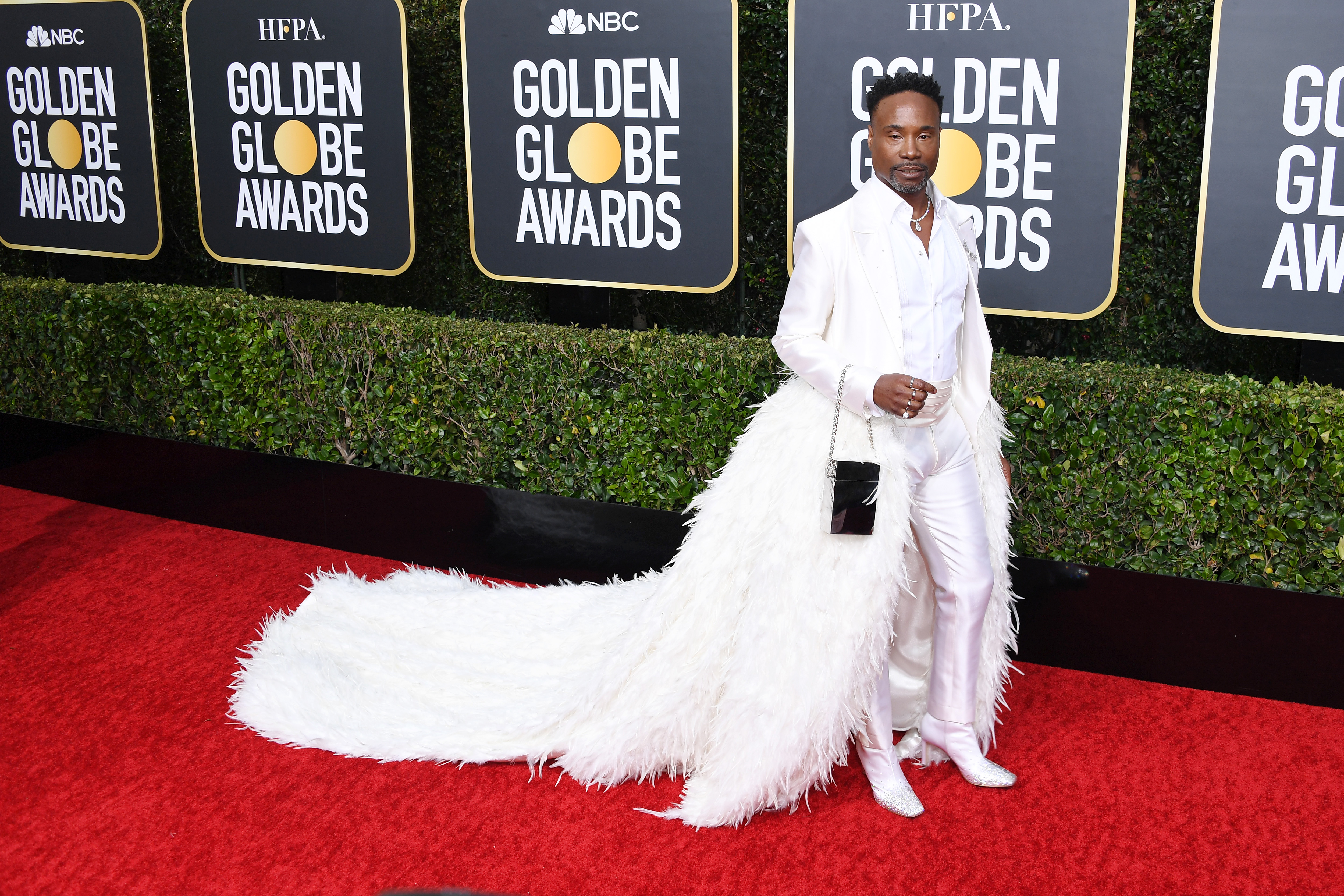 Billy Porter in a white tixuedo with feathered train on the Golden Globes 2019 red carpet