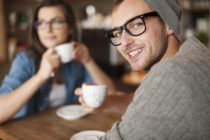 A man smiles at the camera while his girlfriend drinks coffee