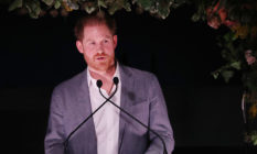 Prince Harry speaking into two microphones