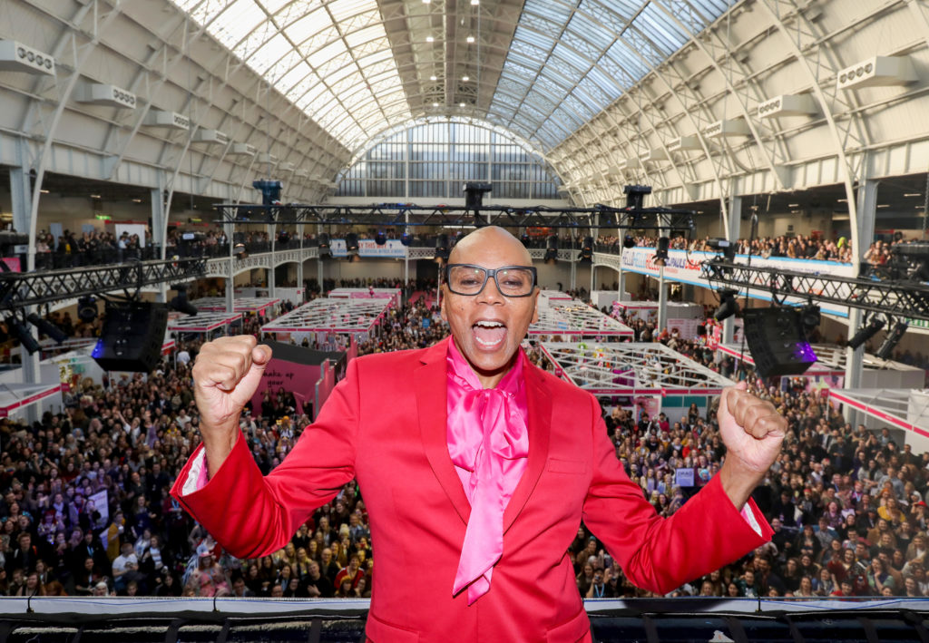 RuPaul standing on a balcony in front of thousands of fans