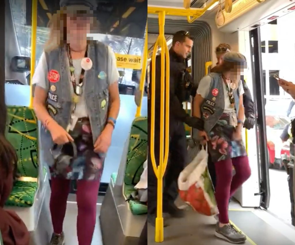 An unidentified woman claimed the 'gay community run the police force' before hurling homophobic slurs and being escorted by Australian Federal Police officers. (Screen captures via YouTube)