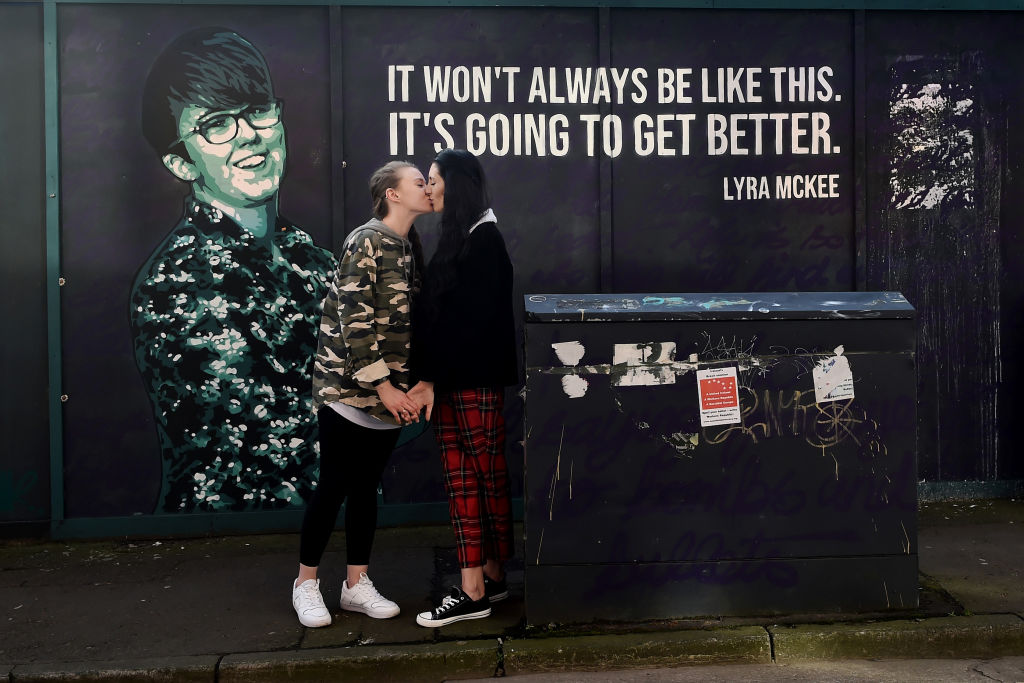 Robyn Peoples and Sharni Edwards, Northern Ireland's first same-sex couple to be legally married embrace and kiss in front of the Lyra McKee mural during a photo call on February 5, 2020 in Belfast, Northern Ireland.